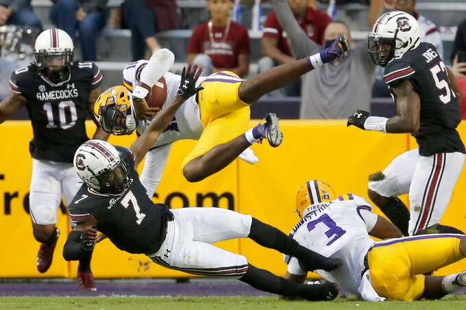 LSU quarterback TJ Finley (11) jumps for yardage against South Carolina during the first half of an NCAA college football game in Baton Rouge, La., Saturday, Oct. 24, 2020. (AP Photo/Brett Duke)
