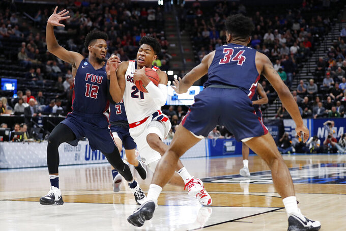 Gonzaga forward Rui Hachimura (21) drives between Fairleigh Dickinson forwards Kaleb Bishop (12) and Mike Holloway Jr. (34) during the first half of a first-round game in the NCAA men's college basketball tournament Thursday, March 21, 2019, in Salt Lake City. (AP Photo/Jeff Swinger)