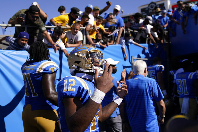 UCLA Bruins wide receiver Matt Sykes (12) greets fans as he leaves the field after an NCAA college football game against Hawaii Saturday, Aug. 28, 2021, in Pasadena, Calif. UCLA won 44-10. (AP Photo/Ashley Landis)