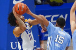 Pittsburgh's Justin Champagnie (11) tries to shoot as North Carolina's Garrison Brooks (15) defends during the first half of an NCAA college basketball game Tuesday, Jan. 26, 2021, in Pittsburgh. (AP Photo/Keith Srakocic)