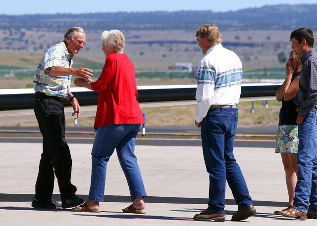 FILE - In this July 11, 2018, file photo, rancher Dwight Hammond Jr., left, is embraced by his wife, Susie Hammond, after arriving by private jet at the Burns Municipal Airport in Burns, Ore. Hammond and his son Steven, convicted of intentionally setting fires on public land in Oregon, were pardoned by President Donald Trump. The U.S. Bureau of Land Management in the final days of the Trump administration issued a grazing permit to Oregon ranchers whose imprisonment sparked the 2016 armed takeover of a federal wildlife refuge by right-wing extremists. (Beth Nakamura/The Oregonian via AP, File)