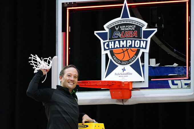 North Texas head coach Grant McCasland celebrates as he cuts down the net after the championship game against Western Kentucky in the NCAA Conference USA men's basketball tournament Saturday, March 13, 2021, in Frisco, Texas. North Texas won 61-57 in overtime. (AP Photo/Tony Gutierrez)