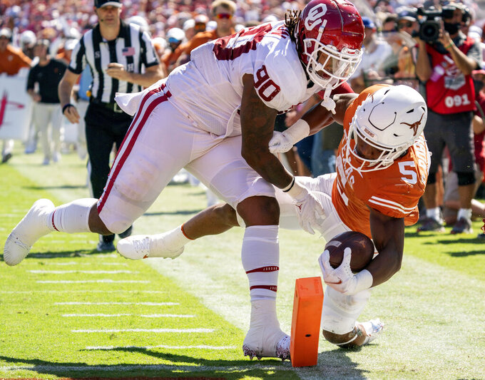 Texas running back Bijan Robinson (5) reaches for the pylon as he is pushed out of bounds by Oklahoma defensive lineman Josh Ellison (90) during the first half of an NCAA college football game at the Cotton Bowl, Saturday, Oct. 9, 2021, in Dallas. Robinson was marked down at the 1-yard line and Texas scored on the next play. (AP Photo/Jeffrey McWhorter)