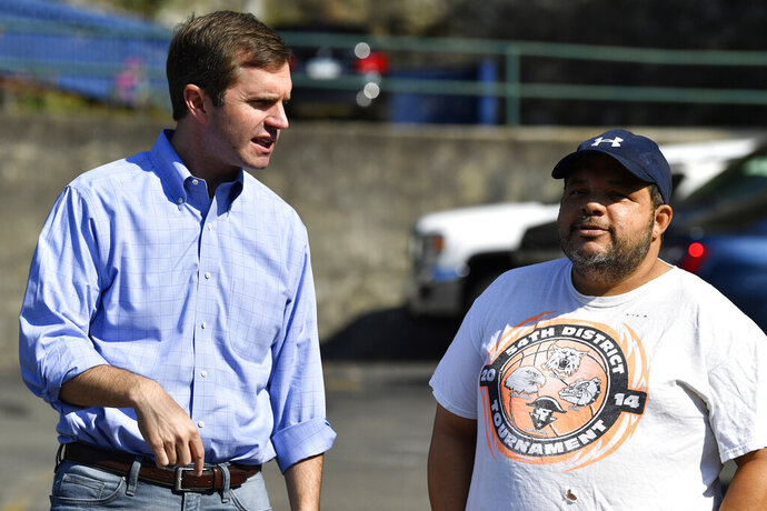 In this Saturday, Sept. 21, 2019, photo, Democratic candidate for governor, Kentucky Attorney General Andy Beshear, left, speaks with a supporter before the start of the Black Gold Festival Parade in Hazard, Ky. Beshear is making a big push for support in eastern Kentucky, a coal-producing region and stronghold for President Donald Trump. (AP Photo/Timothy D. Easley)