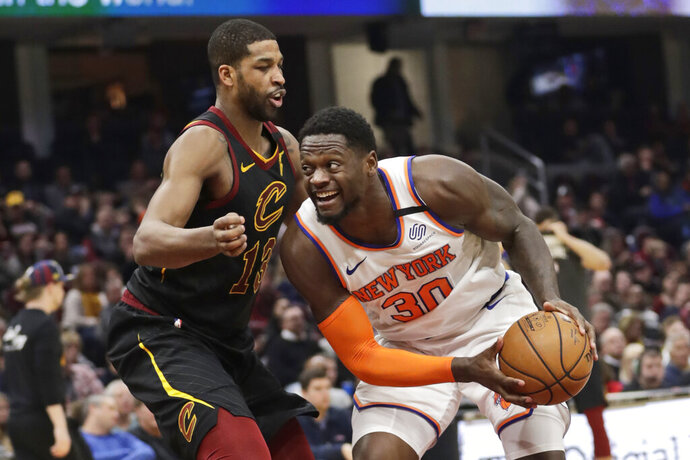 New York Knicks' Julius Randle (30) drives past Cleveland Cavaliers' Tristan Thompson (13) in the second half of an NBA basketball game, Monday, Jan. 20, 2020, in Cleveland. New York won 106-86. (AP Photo/Tony Dejak)
