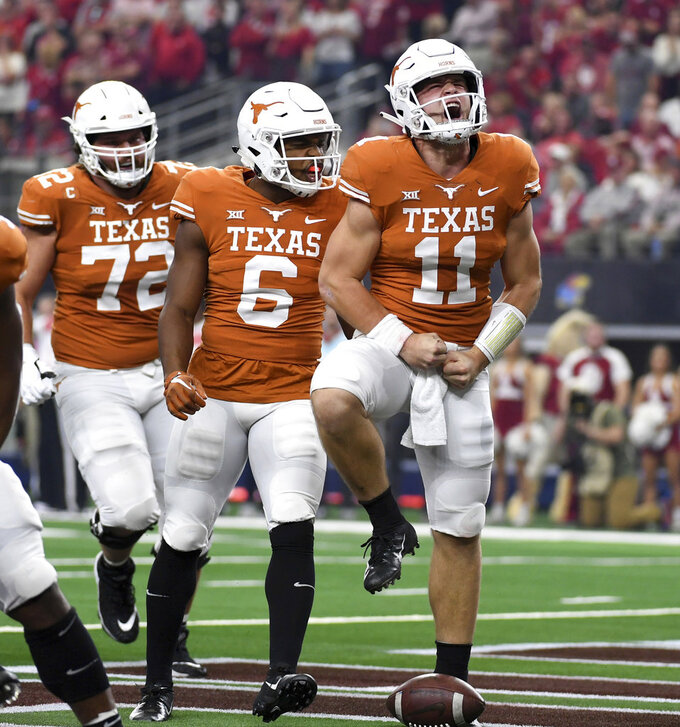 Texas quarterback Sam Ehlinger (11) celebrates after scoring on a touchdown run as Devin Duvernay (6) and Elijah Rodriguez (72) look on during the first half of the Big 12 Conference championship NCAA college football game against Oklahoma on Saturday, Dec. 1, 2018, in Arlington, Texas. (AP Photo/Jeffrey McWhorter)