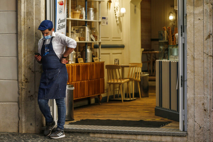 A waiter stands outside a cafe in downtown Rome, Sunday, Oct. 25, 2020. For at least the next month, people outdoors except for small children must now wear masks in all of Italy, gyms, cinemas and movie theaters will be closed, ski slopes are off-limits to all but competitive skiers and cafes and restaurants must shut down in early evenings, under a decree signed on Sunday by Italian Premier Giuseppe Conte, who ruled against another severe lockdown despite a current surge in COVID-19 infections. (Cecilia FabianoLaPresse via AP)