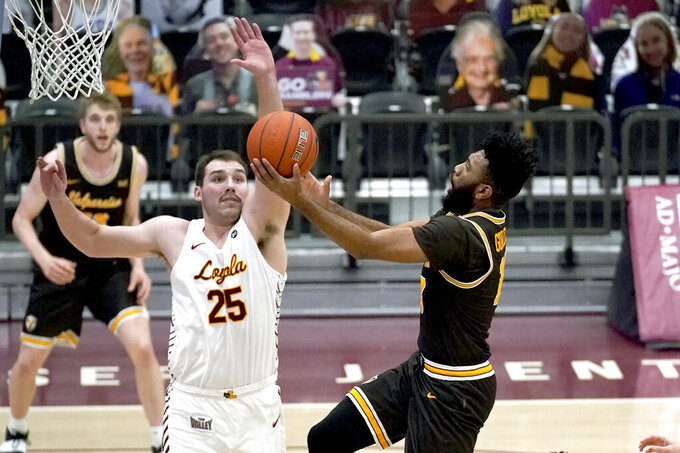 Valparaiso's Eron Gordon, right, drives to the basket past Loyola Chicago's Cameron Krutwig during the first half of an NCAA college basketball game Wednesday, Feb. 17, 2021, in Chicago. (AP Photo/Charles Rex Arbogast)