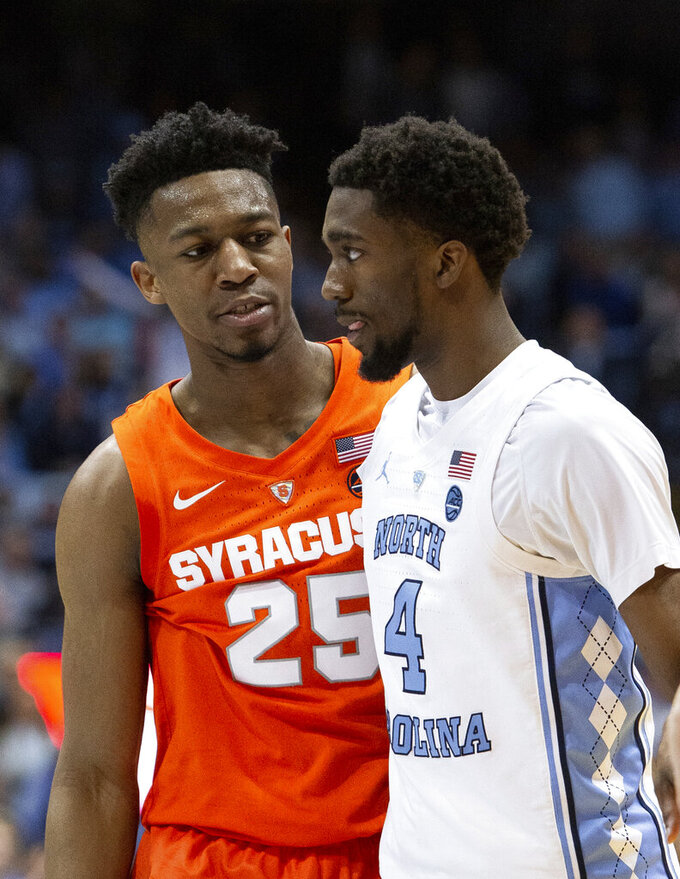 Syracuse's Tyus Battle (25) talks to North Carolina's Brandon Robinson (4) after Battle was fouled during the second half of an NCAA college basketball game in Chapel Hill, N.C., Tuesday, Feb. 26, 2019. (AP Photo/Ben McKeown)