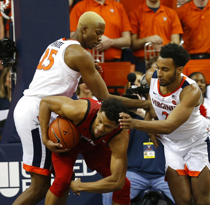 Louisville forward Dwayne Sutton, bottom, battles for a rebound with Virginia forward Mamadi Diakite (25) and Virginia guard Braxton Key (2) during the first half of an NCAA college basketball game in Charlottesville, Va., Saturday, March 9, 2019. (AP Photo/Steve Helber)
