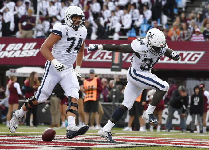 Connecticut running back Kevin Mensah (34) celebrates his touchdown with with teammate Connecticut offensive lineman Ryan Van Demark (74) during the first half of an NCAA college football game against Massachusetts, Saturday, Oct. 26,, 2019, in Amherst, Mass. (AP Photo/Jessica Hill)