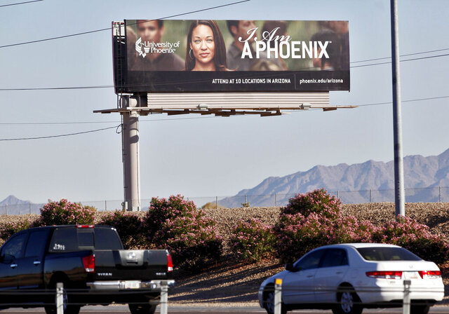 FILE - In this Nov 24, 2009, file photo, a University of Phoenix billboard is shown in Chandler, Ariz. The University of Phoenix for-profit college and its parent company will pay $50 million and cancel $141 million in student debt to settle allegations of deceptive advertisement brought by the Federal Trade Commission. (AP Photo/Matt York, File)