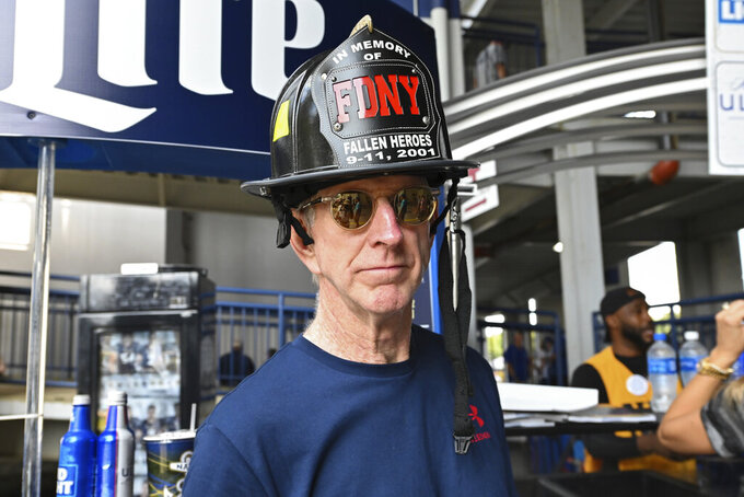 Kevin Connors of Connecticut wears an FDNY fireman helmet while waiting for concessions before an NCAA college football game, between Navy and Air Force, Saturday, Sept. 11, 2021, in Annapolis, Md. (AP Photo/Terrance Williams)