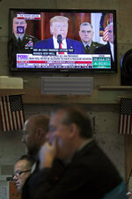 Traders work while a speech by President Donald Trump is displayed on the floor of the New York Stock Exchange in New York, Wednesday, Jan. 8, 2020. (AP Photo/Seth Wenig)