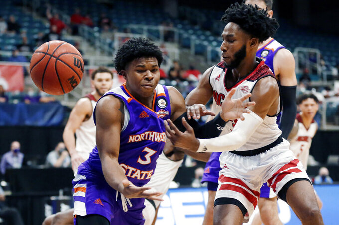 Northwestern State guard Brian White (3) has the ball knocked away on his drive to the basket by Nicholls State guard Kevin Johnson, right, during the second half of an NCAA college basketball game in the Southland Conference semifinals Friday, March 12, 2021, in Katy, Texas. (AP Photo/Michael Wyke)