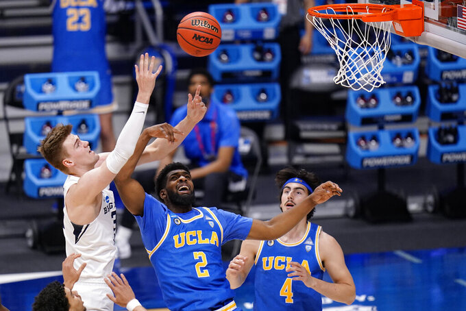 BYU forward Matt Haarms, left, battles for a rebound with UCLA forward Cody Riley (2) and teammate Jaime Jaquez Jr. (4) during the first half of a first-round game in the NCAA college basketball tournament at Hinkle Fieldhouse in Indianapolis, Saturday, March 20, 2021. (AP Photo/AJ Mast)