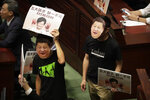 Pan-democratic legislators wearing masks of Chinese President Xi Jinping protest as Hong Kong Chief Executive Carrie Lam attempts to give a policy speech at the Legislative Council in Hong Kong, Wednesday, Oct. 16, 2019. In chaotic scenes, furious pro-democracy lawmakers twice forced Hong Kong's leader to stop delivering a speech laying out her policy objectives and clamored for her to resign after she walked out of the legislature on Wednesday and then delivered the annual address 75 minutes late via television. (AP Photo/Mark Schiefelbein)