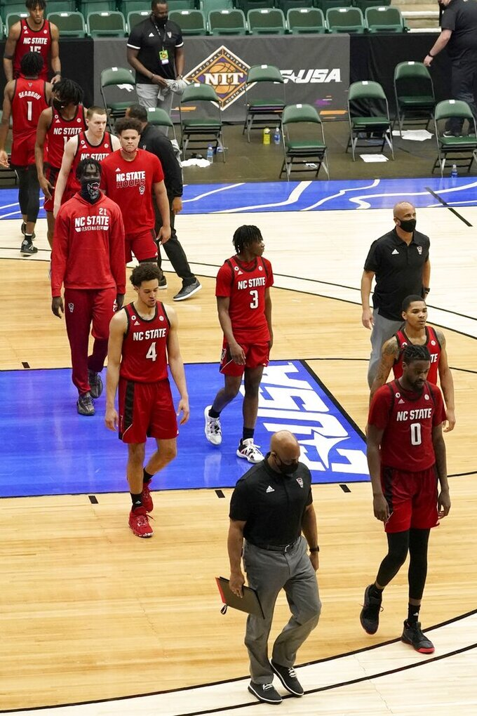 North Carolina State players and staff walk off the court after the team's loss in an NCAA college basketball game to Colorado State in the quarterfinals of the NIT, Thursday, March 25, 2021, in Frisco, Texas. (AP Photo/Tony Gutierrez)