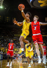 Michigan guard David DeJulius (0) goes to the basket as Houston Baptist forward Jackson Stent (3) defends during the second half of an NCAA college basketball game in Ann Arbor, Mich., Friday, Nov. 22, 2019. Michigan won 111-68. (AP Photo/Tony Ding)
