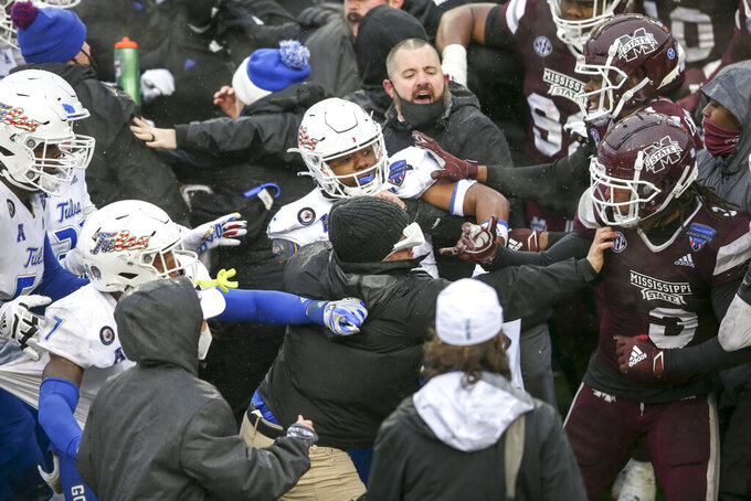 Coaches and staff attempt to separate Tulsa cornerback Reggie Ellis (15) and Mississippi State linebacker Aaron Brule (3) during a postgame fight after Mississippi State's win in the Armed Forces Bowl NCAA college football game in Fort Worth, Texas, Thursday, Dec. 31, 2020. (Ian Maule/Tulsa World via AP)