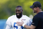 Detroit Lions head coach Dan Campbell greets offensive linebacker Charles Harris before drills at the Lions NFL football camp practice, Wednesday, July 28, 2021, in Allen Park, Mich. (AP Photo/Carlos Osorio)