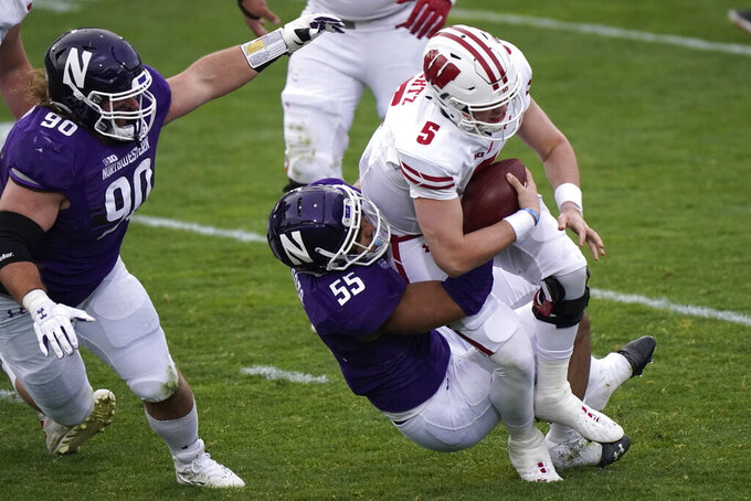 Wisconsin quarterback Graham Mertz is sacked by Northwestern defensive end Eku Leota during the first half of an NCAA college football game in Evanston, Ill., Saturday, Nov. 21, 2020. (AP Photo/Nam Y. Huh)