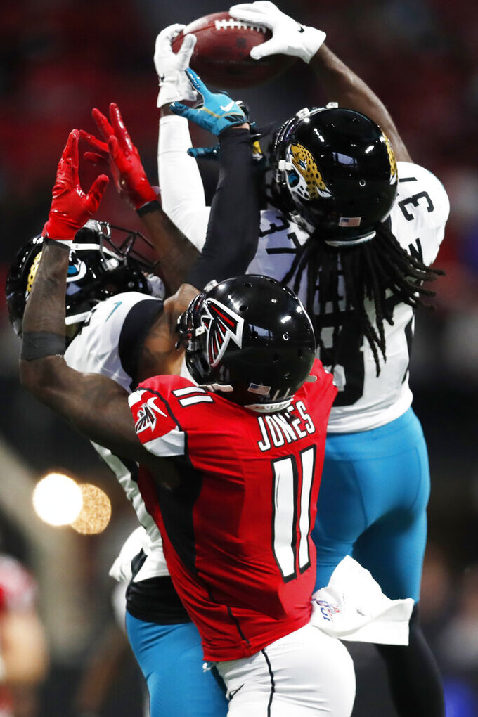 Jacksonville Jaguars cornerback Tre Herndon (37) picks the ball off for an interception against Atlanta Falcons wide receiver Julio Jones (11) during the first half of an NFL football game, Sunday, Dec. 22, 2019, in Atlanta. (AP Photo/John Bazemore)