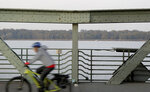 In this Wednesday, Oct. 23, 2019 photo a cyclist drives on the 'Glieniker Bruecke' (Glienicke Bridge) in Potsdam, Germany. During the Cold War, the Glienicke Bridge connecting West Berlin to Potsdam in East Germany was famously used as a site for exchanging captured foreign agents. Since the two opposing sides couldn't agree to work together when the bridge required repairs, each conducted them separately. The paint was applied differently and faded un-uniformly, and the two shades of green meeting at the middle of the bridge are still clearly visible today. (AP Photo/Michael Sohn)