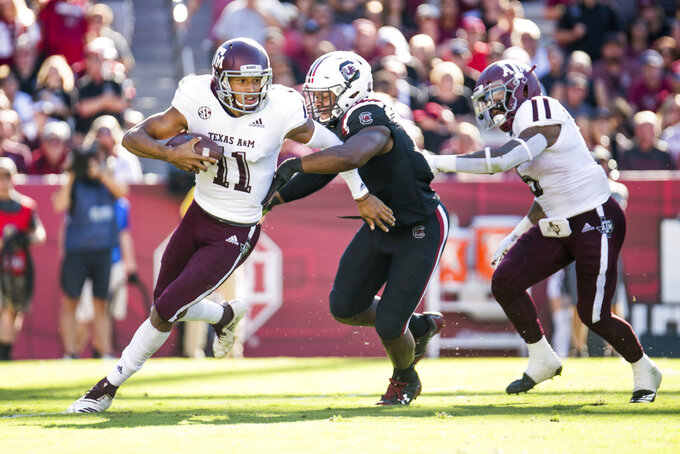 Texas A&M quarterback Kellen Mond (11) runs with the ball against South Carolina defensive lineman Brad Johnson (19) during the first half of an NCAA college football game Saturday, Oct. 13, 2018, in Columbia, S.C. (AP Photo/Sean Rayford)