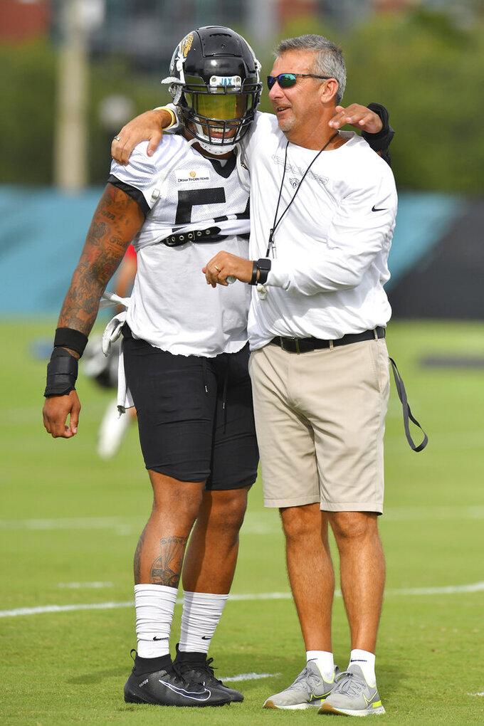 Jacksonville Jaguars head coach Urban Meyer, right, talks with Damien Wilson during an NFL football training camp in Jacksonville, Fla., Tuesday, Aug. 3, 2021. (Bob Self/The Florida Times-Union via AP)