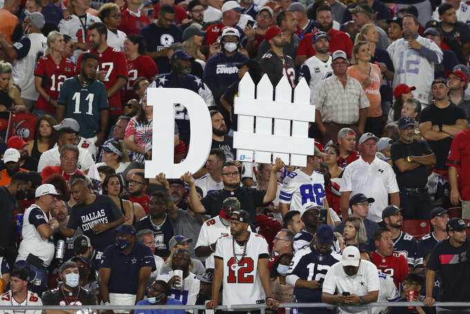 A Tampa Bay Buccaneers fan holds a sign during the first half of an NFL football game against the Dallas Cowboys Thursday, Sept. 9, 2021, in Tampa, Fla. (AP Photo/Mark LoMoglio)