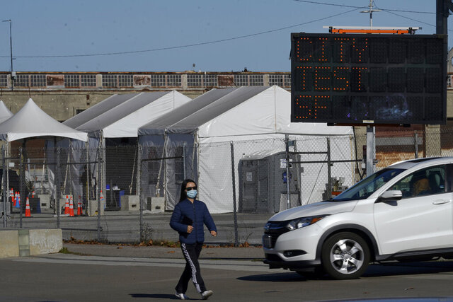 A pedestrian wears a face mask while walking past a car exiting the CityTestSF at Pier 30/32 COVID-19 testing site during the coronavirus pandemic in San Francisco, Wednesday, Dec. 23, 2020. (AP Photo/Jeff Chiu)