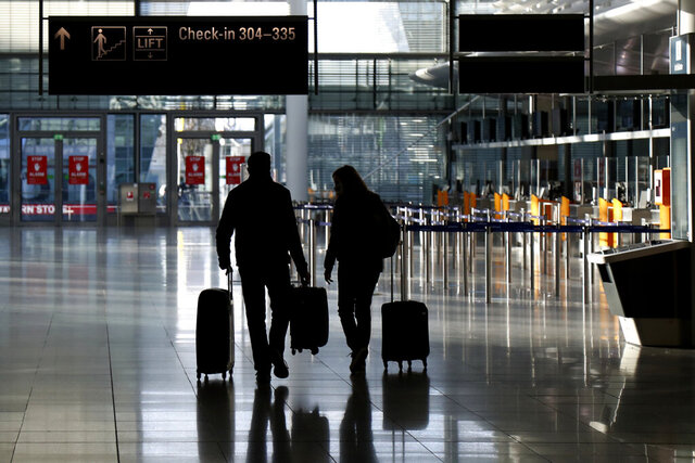 FILE - In this Saturday, Dec. 26, 2020 file photo, people walk with their luggage through a deserted check-in hall at the airport in Munich, Germany as Germany continues its second lockdown to avoid the further outspread of the coronavirus. On Tuesday, Jan. 12, 2021, the U.S. government said it will require airline passengers entering the country to show proof of a negative COVID-19 test before boarding their flights. It will take effect Jan. 26. (AP Photo/Matthias Schrader)