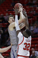 UC Davis center Matt Neufeld, left, shoots as Utah center Lahat Thioune (32) defends during the first half of an NCAA college basketball game Friday, Nov. 29, 2019, in Salt Lake City. (AP Photo/Rick Bowmer)