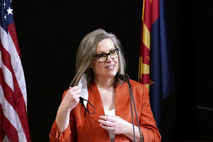 FILE - In this Monday, Dec. 14, 2020, file photo, Arizona Secretary of State Katie Hobbs removes her face mask as she addresses the members of Arizona's Electoral College prior to them casting their votes, in Phoenix. Hobbs says voting machines from the state's most populous county should not be used after they were handed over to state Senate Republicans for an audit of the 2020 election results. (AP Photo/Ross D. Franklin, File)