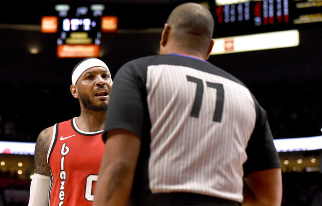 Portland Trail Blazers forward Carmelo Anthony, left, has some words with referee Karl Lane, right, during the first quarter of the team's NBA basketball game against the Phoenix Suns in Portland, Ore., Tuesday, March 10, 2020. (AP Photo/Steve Dykes)