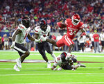 Houston running back Mulbah Car (34) is tripped up by Texas Tech defensive back Reggie Pearson Jr. (22) during the first half of an NCAA college football game Saturday, Sept. 4, 2021, in Houston. (AP Photo/Justin Rex)