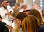 Participants of the Future Investment Initiative forum follow the news during the opening in Riyadh, Saudi Arabia, Tuesday, Oct. 29, 2019. The long-planned initial public offering of a sliver of Saudi Arabia's state-run oil giant Saudi Aramco will see shares traded on Riyadh's stock exchange in December, a Saudi-owned satellite news channel reported Tuesday as the kingdom's marquee investment forum got underway. (AP Photo/Amr Nabil)