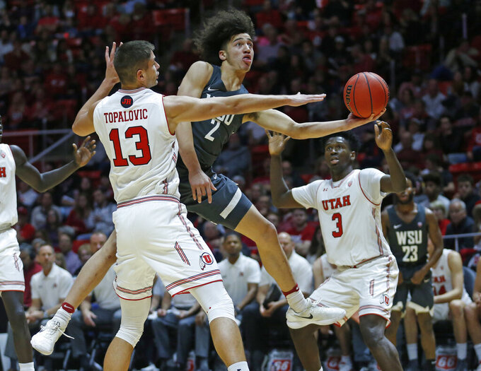 Washington State forward CJ Elleby (2) lays up the ball as Utah's Novak Topalovic (13) and Donnie Tillman (3) defend during the first half of an NCAA college basketball game Saturday, Jan. 12, 2019, in Salt Lake City. (AP Photo/Rick Bowmer)