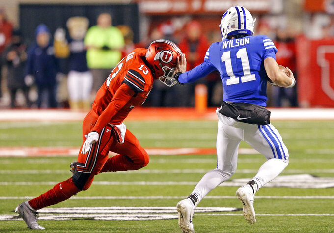 BYU quarterback Zach Wilson (11) stiff arms Utah defensive back Marquise Blair (13) as he carries the ball in the first half during an NCAA college football game Saturday, Nov. 24, 2018, in Salt Lake City. (AP Photo/Rick Bowmer)