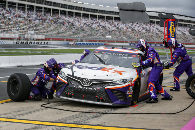 Denny Hamlin's pit crew works on his car during a pit stop in a NASCAR Cup Series auto race at Charlotte Motor Speedway in Concord, N.C., Sunday, Oct. 11, 2020. (AP Photo/Nell Redmond)