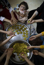 Palestinian women prepare sweets ahead of the Muslim Eid al-Adha holiday in the West Bank city of Nablus, Monday, July. 19, 2021. Eid al-Adha, or Feast of Sacrifice, Islam's most important holiday marks the willingness of the Prophet Ibrahim (Abraham to Christians and Jews) to sacrifice his son, starts on Tuesday with Muslims slaughtering animals and celebrating the end of their annual hajj pilgrimage to the holy city of Mecca in Saudi Arabia. (AP Photo/Majdi Mohammed)