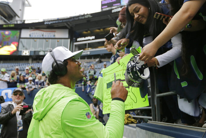 Seattle Seahawks quarterback Russell Wilson  gives autographs before an NFL football game against the Cincinnati Bengals, Sunday, Sept. 8, 2019, in Seattle. (AP Photo/John Froschauer)