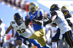 UCLA running back Brittain Brown, center, runs the ball for a touchdown past California safety Daniel Scott, left, and Elijah Hicks during the second half of an NCAA college football game against California in Los Angeles, Sunday, Nov. 15, 2020. UCLA won 34-10. (AP Photo/Kelvin Kuo)