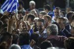 Greek opposition New Democracy party leader Kyriakos Mitsotakis, center right, is surrounded by supporters at the end of his main election campaign rally in Athens, on Thursday, July 4, 2019. Greeks head to the polls in early general elections on Sunday, July 7. (AP Photo/Thanassis Stavrakis)