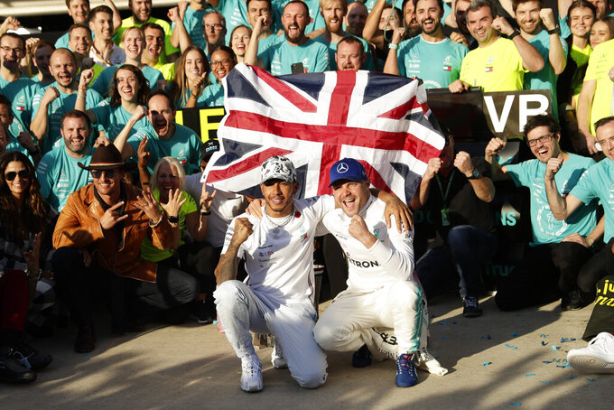 Mercedes driver Lewis Hamilton, left, of Britain, and Mercedes driver Valtteri Bottas, of Finland, celebrate following the Formula One U.S. Grand Prix auto race at the Circuit of the Americas, Sunday, Nov. 3, 2019, in Austin, Texas. (AP Photo/Eric Gay)
