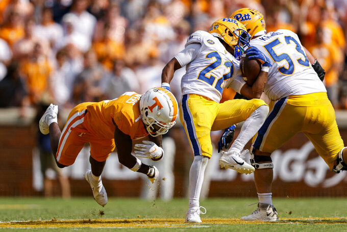 Pittsburgh running back Vincent Davis (22) spins away from Tennessee defensive back Trevon Flowers (1) during the second half of an NCAA college football game Saturday, Sept. 11, 2021, in Knoxville, Tenn. (AP Photo/Wade Payne)