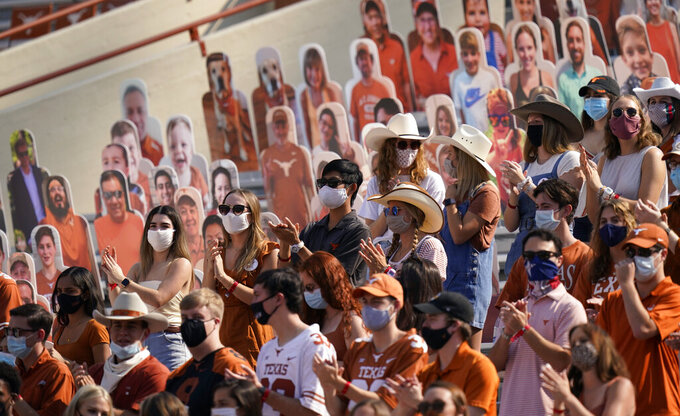 Fans wear face masks during the first half of an NCAA college football game between Texas and TCU, Saturday, Oct. 3, 2020, in Austin, Texas. (AP Photo/Eric Gay)
