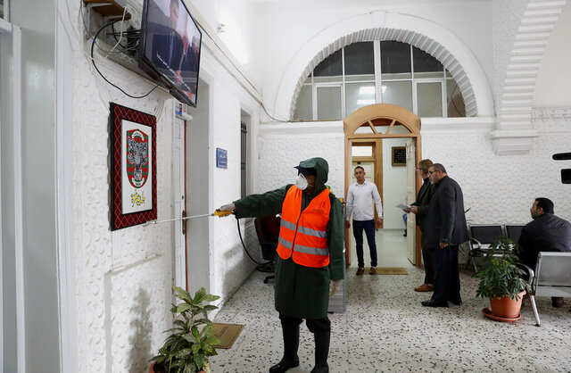 A worker wearing protective gear disinfects the offices at the building of Gaza municipality to help prevent the spread of the new coronavirus, in Gaza City, Tuesday, March 10, 2020.  For most people, the new coronavirus causes only mild or moderate symptoms, such as fever and cough. For some, especially older adults and people with existing health problems, it can cause more severe illness, including pneumonia. (AP Photo/Adel Hana)