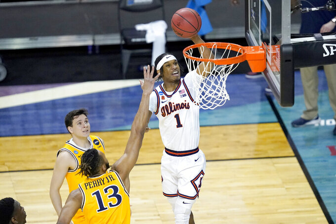 Illinois 's Trent Frazier (1) scores past Drexel's Tim Perry Jr. (13) during the first half of a first round NCAA college basketball tournament game Friday, March 19, 2021, at the Indiana Farmers Coliseum in Indianapolis .(AP Photo/Charles Rex Arbogast)